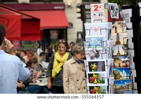 PARIS, FRANCE - MAY 2016 : Postcard shop with Parisian calling using cell phone on May 21, 2016 in Paris, France