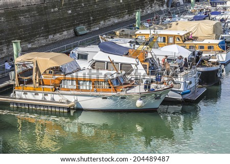 PARIS, FRANCE - MAY 18, 2014: Row of houseboats docked on Canal Saint Martin - a 4,5 km long canal, it connects canal de l'Ourcq to river Seine.