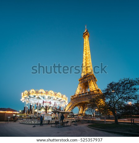 PARIS, FRANCE - NOVEMBER 29, 2016: The Eiffel Tower (Tour Eiffel) illuminated at dusk with carousel. It's a wrought iron lattice tower named after the engineer Gustave Eiffel.