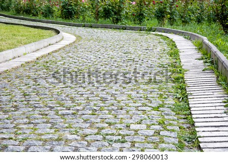 Park walkway of paving stones with rose bushes in the background.