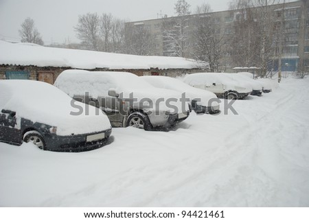 Parked cars covered with snow in the winter blizzard on the street of city