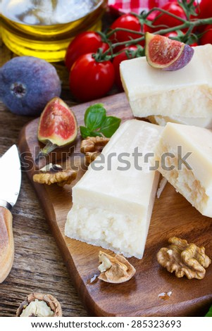 parmesan cheese on wooden cutting board with cherry tomatoes, walnuts and figues
