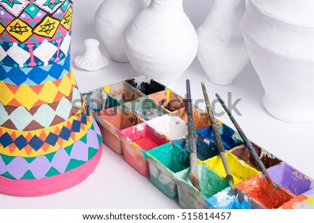 Part of a pottery painting art studio consists of color palette, brushes, and unfinished pottery craft vases on white background