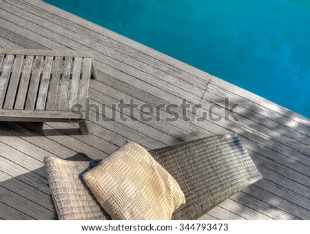 partial view from a luxury pool with wooden chairs and deck. Partial uncolored