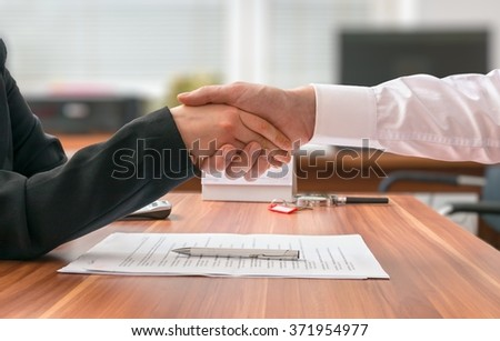 Partnership concept. Businessman and woman sitting behind desk with agreement and shaking hands on blurred background.