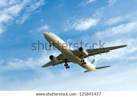 Passenger airplane landing against blue cloudy sky
