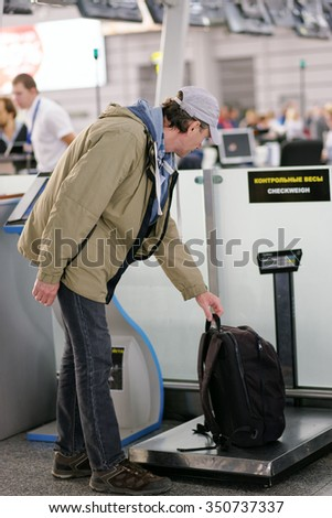 Passenger checking the weight of his luggage in the airport before the check-in
