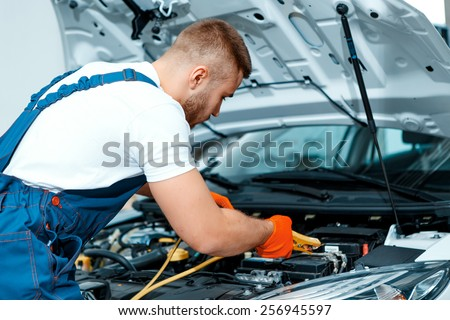 Passionate about cars. Handsome muscular car mechanic in uniform checking the engine in car service station