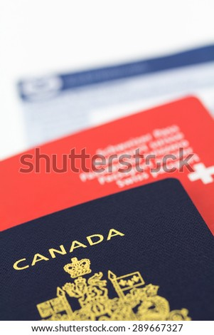 Passports with immigration form. Canadian in focus and  Swiss with light blur.