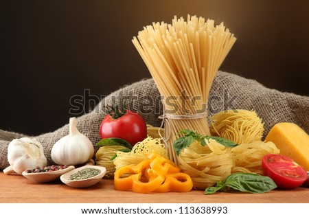 Pasta spaghetti, vegetables and spices, on wooden table, on brown background