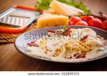 Pasta with ingredients on wood background