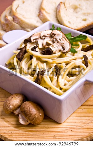 Pasta with mushrooms, bread on a wood table