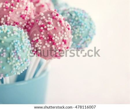 Pastel color cake pops in a blue cup with hazy vintage editing