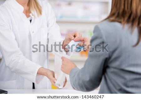 Patient pays for the medicine to the pharmacist with a twenty euro note while receiving the bag