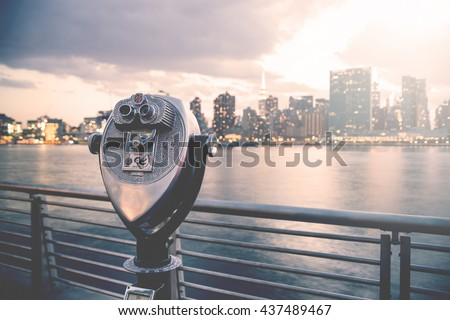 Pay binoculars in Long Island City with the Manhattan skyline at sunset in the background. travel, vacation, sightseeing, new york, tourism, and urban living concept