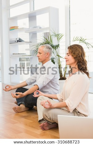 Peaceful casual business colleagues meditating in the office