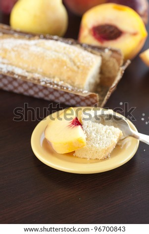 peach, pear, plum, coconut cake and spoon on a wooden table