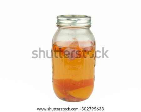 peach, strawberry fruit flavored moonshine alcohol in a mason jar