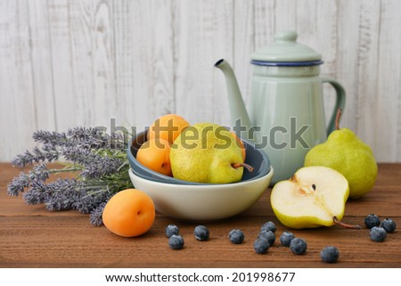Pear in bowl with fresh blueberry, apricot and lavender flowers on wooden background