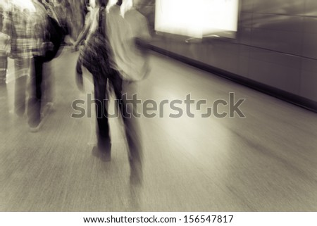 Pedestrians walking in station aisle abstract blur