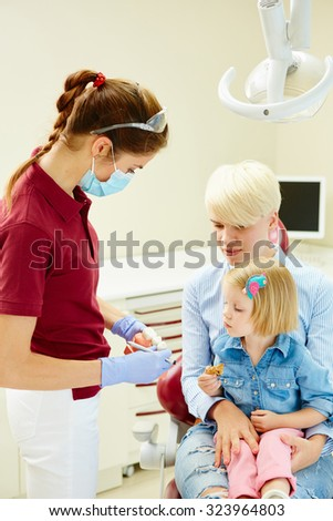 Pediatric dentist explaining to young patient and her mother the model in dental clinic