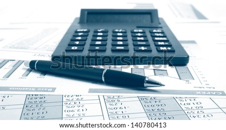 Pen and calculator on paper table with finance report