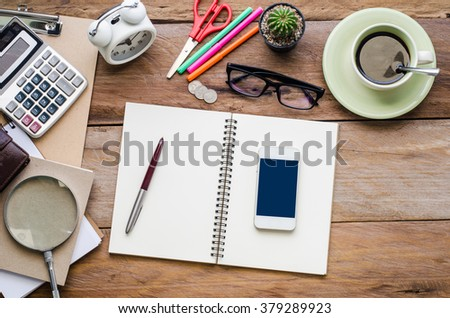 Pen and smart phone on a blank notebook and stationery on wooden table.