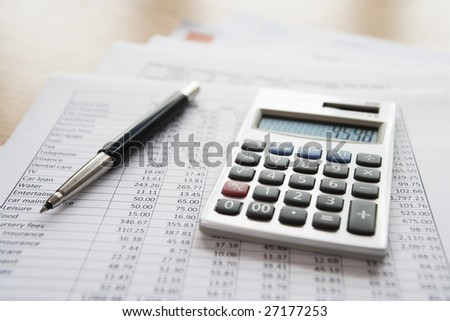 Pen & calculator on personal finance documents.  Logos, numbers, signature etc have been removed or changed to make unidentifiable