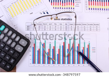 Pen, glasses and calculator on financial chart, business concept, analysis of sales plan, business report, business work station with paperwork