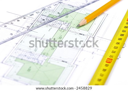 Pencil, tape measure and a ruler on top of a floor plan; Focus on pencil's tip.