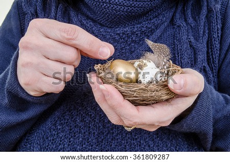 Pension fund or retirement withdrawal. Woman holding a nest full of eggs and picking out the golden one. Close up.