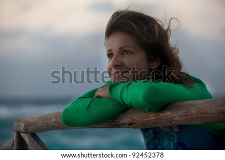 Pensive beautiful young woman on the beach