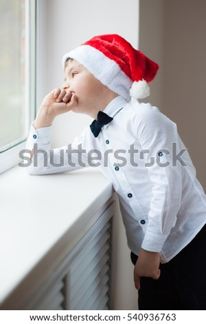 pensive boy in santa hat and bow tie at the window in Christmas Eve