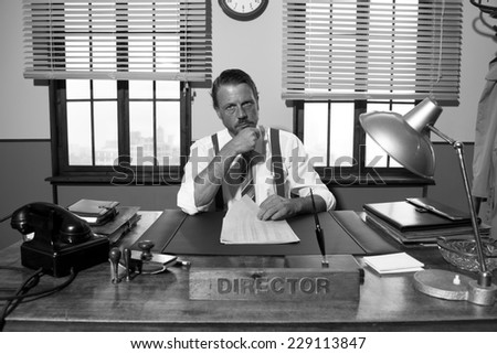 Pensive director with hand on chin working at office desk, 1950s style.