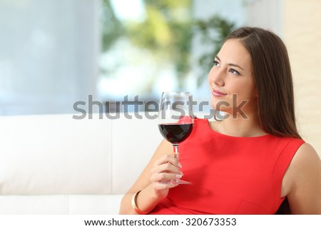 Pensive relaxed fashion woman in red with a cup of wine sitting on a couch at home