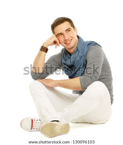 Pensive stylish young man sitting on floor and looking at copyspace , isolated on white background