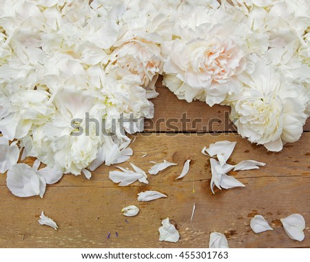 Peony petals lying on wooden background