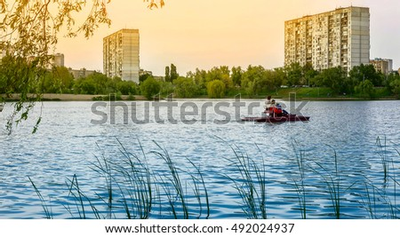 People are sailing on a catamaran on the lake on the background of high-rise buildings at sunset. Ukraine, Kiev, Lake Telbin.
