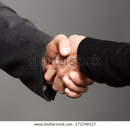 People at work: man and woman hand shaking.