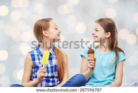 people, children, friends and friendship concept - happy little girls eating ice-cream over holidays lights background