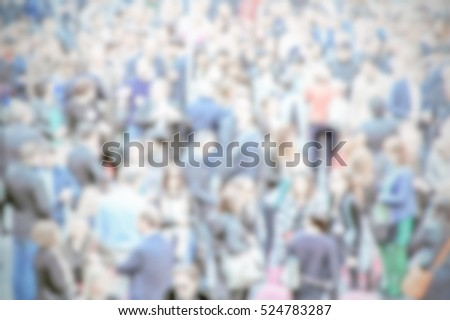People crowd background with an intentional blur effect applied. Humans and location not recognizable.