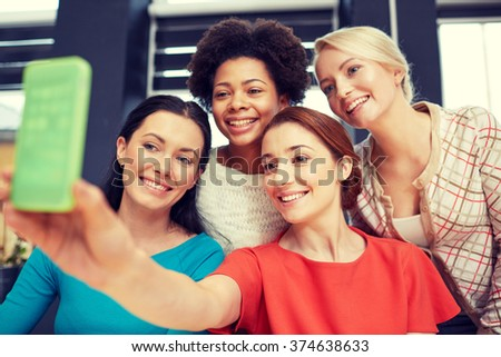 people, leisure, friendship and technology concept - happy young women taking selfie with smartphone