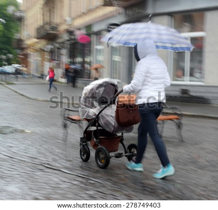 People on the streets of the city on a rainy day in motion blur