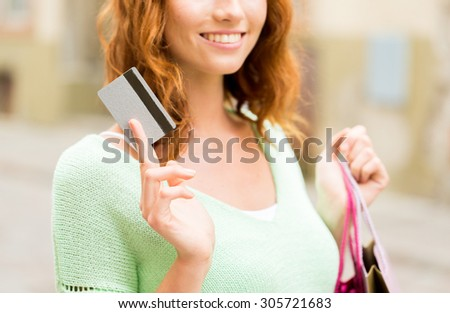 people, sale and consumerism concept - close up of happy woman with shopping bags and credit card on city street