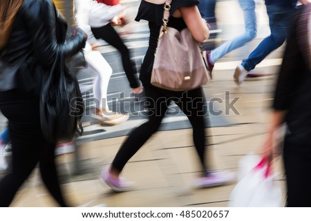 people shown in motion blur crossing a street in the city