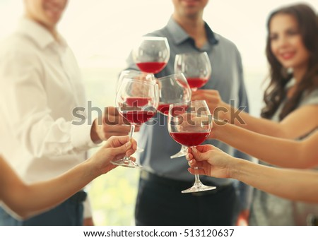 People toasting with glasses of red wine, closeup