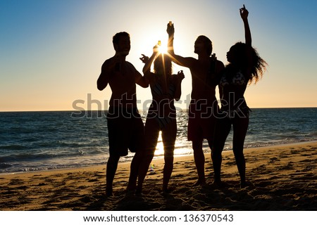 People (two couples) on the beach having a party, drinking and having a lot of fun in the sunset (only silhouette of people to be seen, people having bottles in hands with the sun shining through)