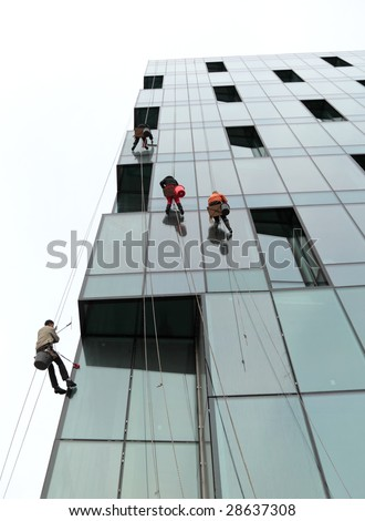 People wash windows of office building