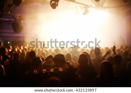 People with hands up having fun at a music concert