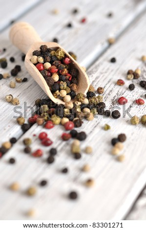 Peppercorn mix in a wooden scoop on an old white table